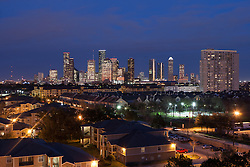 Houston, Texas skyline in early evening from west with residential neighborhood in foreground.