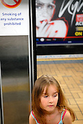 """Child (6 years old) near unusual """"no smoking"""" sign, with woman smoking on billboard in background. Sydney, Australia"""
