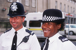 Police man and woman wearing uniforms standing in street smiling,