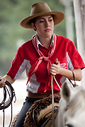 Young Brazilian Gaucha cowgirl female, riding horses, preparing to compete in a rodeo. Gaucho cowboy Rodeo, Flores de Cunha, Rio Grande do Sul.