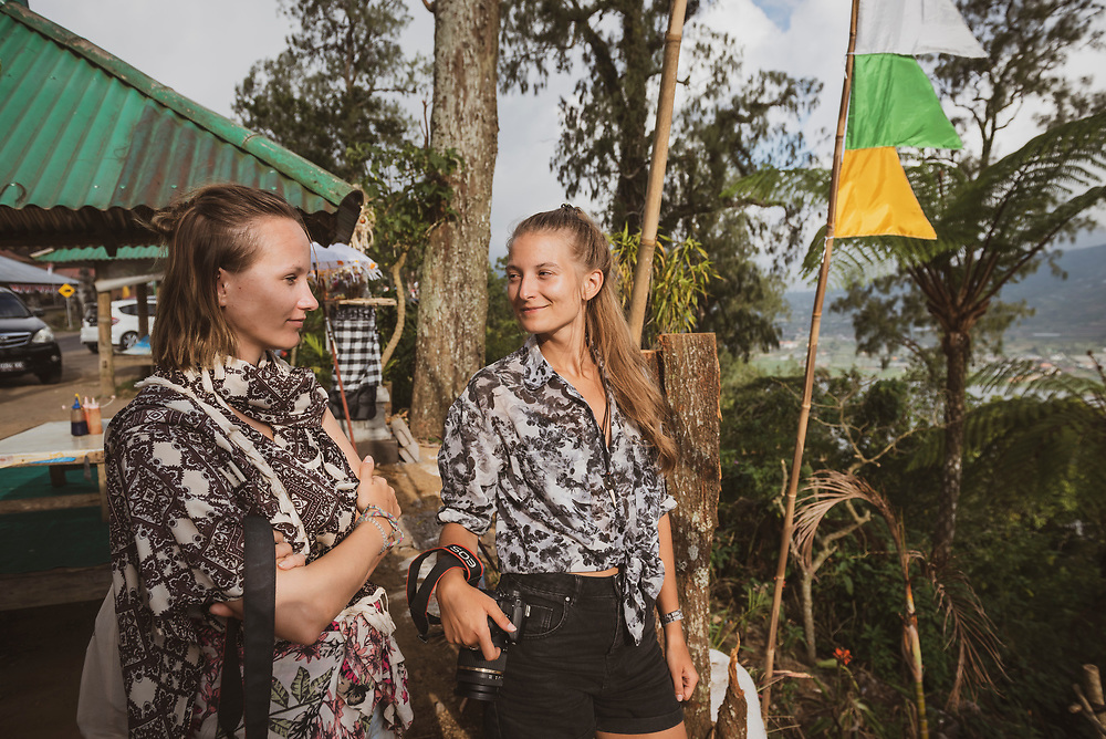 Bali, Indonesia - September 22, 2017: Two friends from Germany visiting Bali make a stop on a day-long road trip to enjoy the beautiful view high above Lake Buyan.