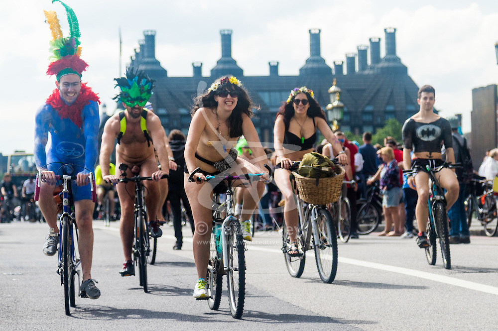 Westminster Bridge, London, June 11th 2016. Hundreds of naked and semi-naked cyclists participate in the World Naked Bike Ride that takes place in cities around the world, to highlight the alternatives to hydrocarbon fuels. PICTURED: Portcullis House makes a badkdrop as naked cyclists cross Westminster Bridge.