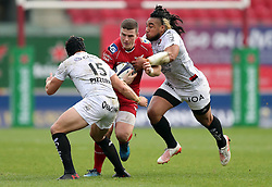 Scarlets' Scott Williams (centre) is tackled by RC Toulon's Leigh Halfpenny (left) and Ma'a Nonu during the European Champions Cup, pool three mach at Parc y Scarlets, Llanelli.