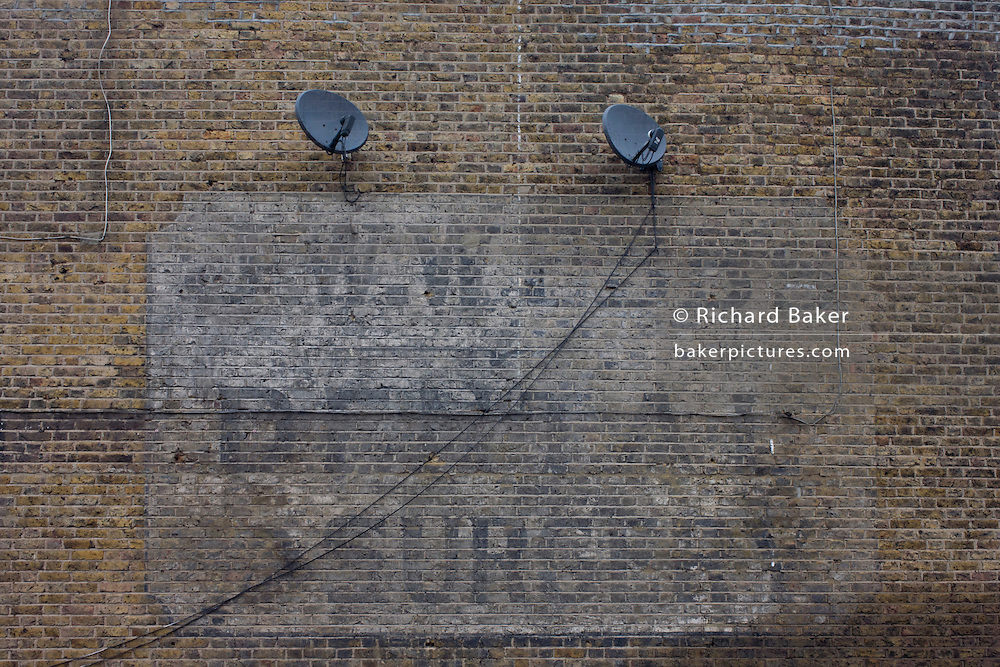 Old century advertising for a former dentist business fading on a brick wall in east Dulwich, south London.