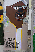 "An image of Omar al-Bashir, President of Sudan, adorns an old section of the old Berlin Wall opposite the former Checkpoint Charlie, the former border between Communist East and West Berlin during the Cold War. The Berlin Wall was a barrier constructed by the German Democratic Republic (GDR, East Germany) starting on 13 August 1961, that completely cut off (by land) West Berlin from surrounding East Germany and from East Berlin. The Eastern Bloc claimed that the wall was erected to protect its population from fascist elements conspiring to prevent the ""will of the people"" in building a socialist state in East Germany. In practice, the Wall served to prevent the massive emigration and defection that marked Germany and the communist Eastern Bloc during the post-World War II period."