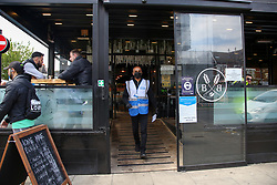© Licensed to London News Pictures. 17/05/2021. London, UK. A member of the NHS COVID-19 Test and Trace leaves a cafe in north London after speaking with the owner about displaying the QR code poster at the entrance of the cafe. Displaying an official NHS QR code poster and collecting contact details for NHS Test and Trace is a legal requirement for hospitality services (including pubs, bars, restaurants and cafés), close contact services (including hairdressers and barber shops) and community centres. Photo credit: Dinendra Haria/LNP