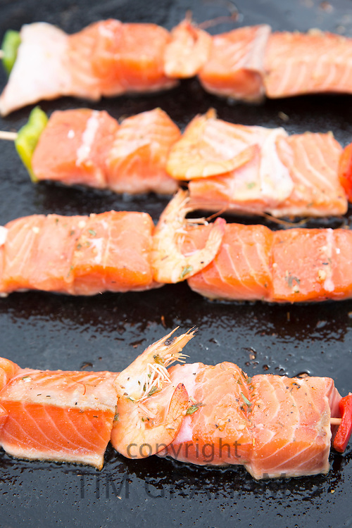 Grilled salmon fillets and prawns healthy fast food cooked on griddle for sale at street market Bordeaux, France