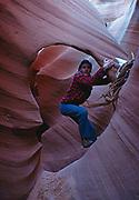 Fred Hirschmannclimbing through pothole arch in slot canyon, Colorado Plateau.