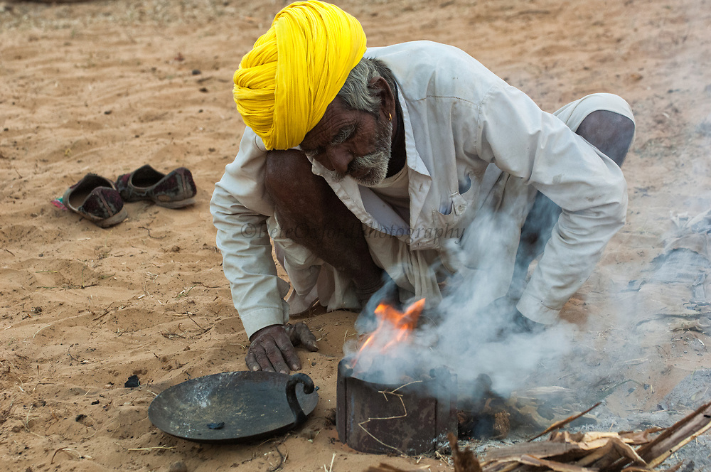 Rajusthani pastoralist cooking his dinner at the Pushkar camel and livestock fair which takes place in the Hindu month of Kartik (October / November) ten days after Diwali (Festival of Lights). Pushkar has always been the the region's main market for herdsman and farmers buying and selling camels, horses, indigenous breeds of cattle and even elephants. Over the years this annual trading event has increased in volume to become one of the largest in Asia. Temporary tents and campsites suddenly appear to accomodate the thousands of pilgrims, villagers and tourists. Entertainers and contests abound and a festive funfair atmosphere prevails over Pushkar during the Mela's 2 week duration. Thousands of men come first with their camels, horses and cattle and camp on the dunes to transact business. 3 days before the full moon the women arrive beautifully attired. The town of Pushkar is one of the holiest centers of Hinduism and houses one of the few Brahma Temples in India. It is one of the 5 essential pilgrimage centers which a Hindu must visit in his lifetime along with Badrinath, Puri, Rameshwaram and Dwarka. The 12 day fair culminates in a religious Hindu pilgrimage and reaches a crescendo on the night of the full moon (Purnima) when pilgrims take a dip in the holy lake.  <br /> Pushkar, Rajasthan. INDIA