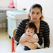 Milan, Italy, May 2008. Centre for immigrant women's health, San Carlo Hospital. Cynthya , Peruvian mother and her daughter during the meeting with the cultural mediator and the pediatrician...Milano, Italia, Maggio 2008. Centro di salute e ascolto donne immigrate, Ospedale San Carlo. Cynthya, mamma Peruviana con la figlia, durante il colloquio di accompagnamento alla crescita con la mediatrice culturale e la pediatra.