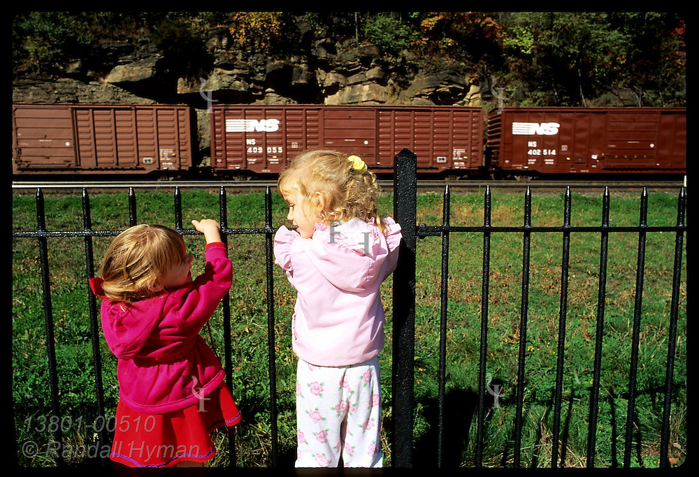 Two girls hang on fence to watch passing train at Horseshoe Curve public viewing area; Altoona. Pennsylvania