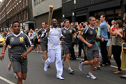 © Licensed to London News Pictures. 21/07/2012, London, UK.  Rapper, songwriter and record producer, Dizzee Rascal in his socks after discarding his trainers carries the London 2012 Olympic Torch at Shoreditch in London during the Olympic Torch Relay, Saturday, July 21, 2012. Photo credit : Sang Tan/LNP