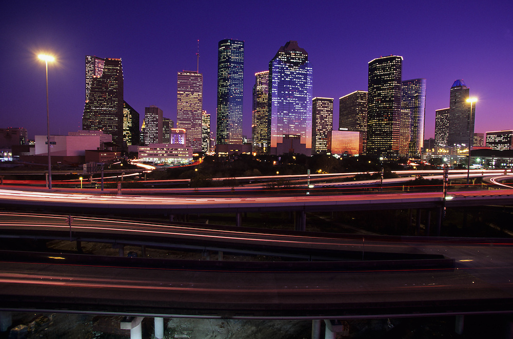 Night traffic motion blur on freeway passing the western side of the Houston, Texas skyline.