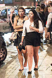 """© Licensed to London News Pictures . 20/12/2014 . Manchester , UK . Two women walk on the pavement outside Deansgate Locks nightclub venue . """" Mad Friday """" revellers out in the rain and cold in Manchester . Mad Friday is typically the busiest day of the year for emergency services , taking place on the last Friday before Christmas when office Christmas parties and Christmas revellers enjoy a night out .  Photo credit : Joel Goodman/LNP"""