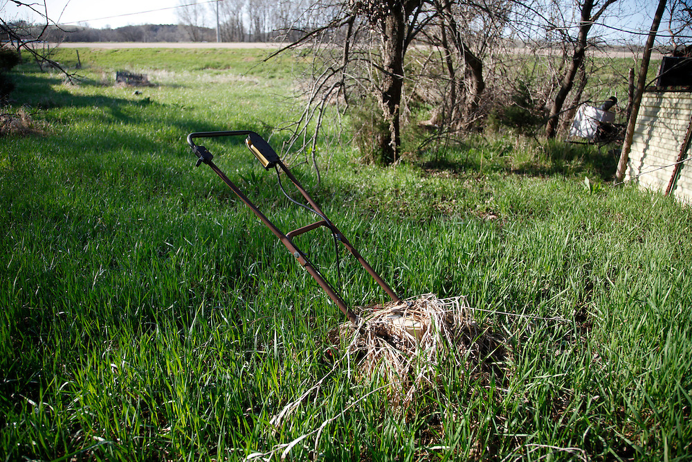 An abandoned lawnmover is overgrown with grass in the yard of a decaying house in Monowi, Nebraska April 28, 2011. At its peak in the 1930's the town had 150 residents but after the railroad left it began to decline. Now down to a population of just one, Monowi is the only incorporated town, village or city in the United States with just a single resident.  REUTERS/Rick Wilking (UNITED STATES)