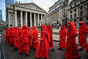 """While the """"Blood Money March"""" protest of the Extinction Rebellion was ongoing across the city of London, the Red Rebel Brigades marched towards the Bank of England on Friday, Aug 27, 2021.<br /> It is an international performance """"artivist"""" troop dedicated to illuminating the global environmental crisis and supporting groups and organizations fighting to save the planet. (VX Photo/ Vudi Xhymshiti)"""