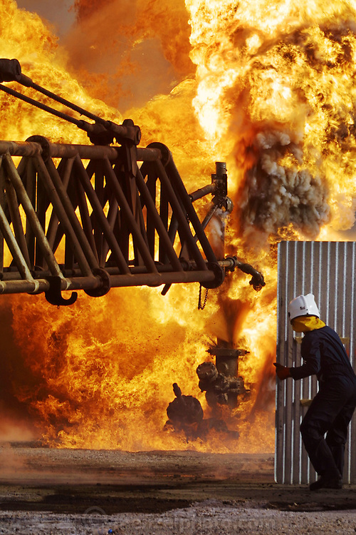 """Two Kuwaiti Oil Company firefighters shelter themselves from the intense heat of an oil well fire in a spray of water, behind a piece of metal roofing as they guide a """"stinger"""" on the end of a long boom that will pump drilling mud into the gushing well at high pressure to stop the fire and flow of gas and oil. Rumaila oilfield, southern Iraq. The Rumaila field is one of Iraq's biggest with 5 billion barrels in reserve. Many of the wells are 10,000 feet deep and produce huge volumes of oil and gas under tremendous pressure, which makes capping them very difficult and dangerous. Rumaila is also spelled Rumeilah."""