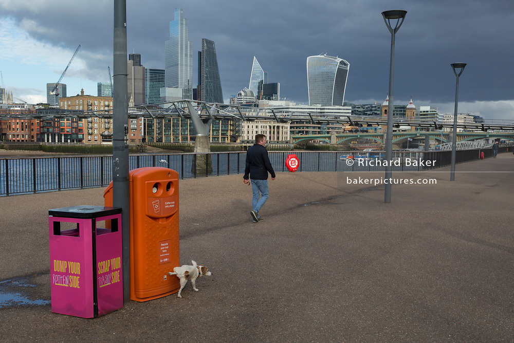 As the UK government announces further Coronavirus-related restrictions to its citizens, with the immediate closure of pubs, cafes, gyms and cinemas, and the worldwide number of deaths reaching 10,000 with 240,000 cases, 953 of those in London alone, a terrier dog pees aganist a pavement bin on a largely deserted Millennium Walk on the Southbank, on 20th March 2020, in London, England.