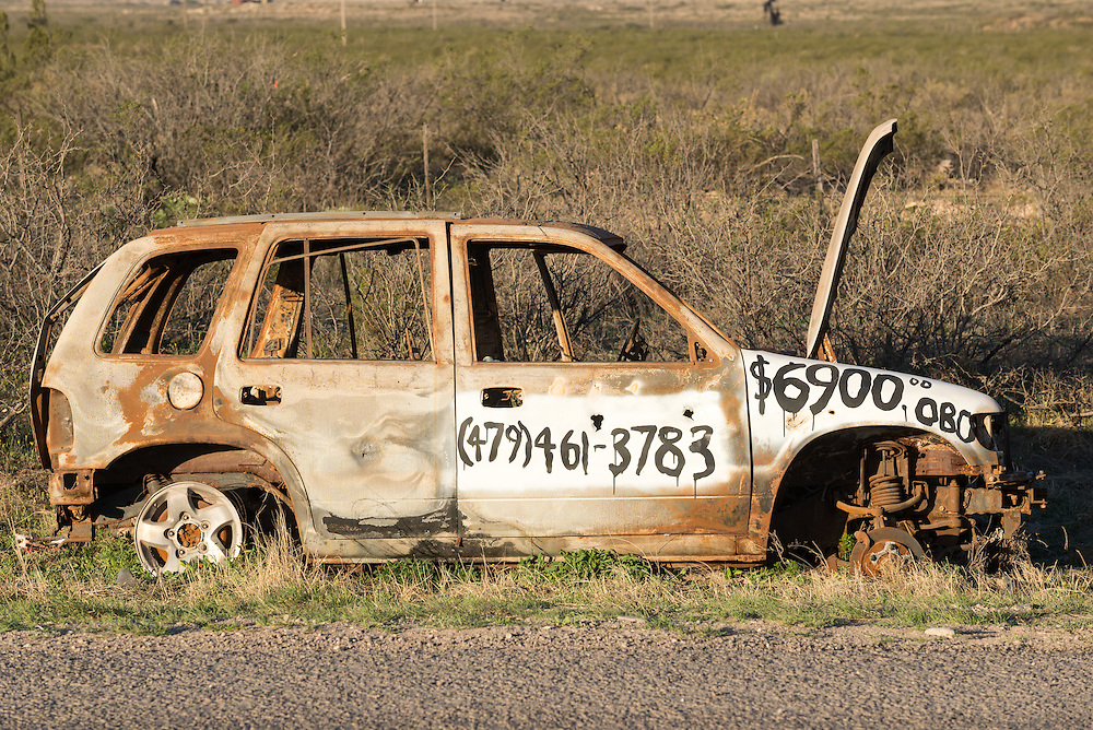 Humorous for sale sign painted on abandoned car on the side of road in West Texas.