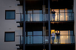 Members of the public clap on their balconies in Canary Wharf, London to salute local heroes during Thursday's nationwide Clap for Carers NHS initiative to applaud NHS workers fighting the coronavirus pandemic.