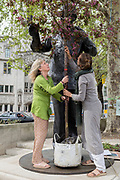 Women campaigners position a large potted tree at the feet of Nelson Mandela's statue in Parliament Square during the week-long protest by climate change activists with Extinction Rebellion's campaign to block road junctions and bridges around the capital, on 23rd April 2019, in London England.