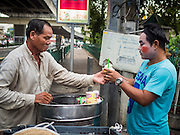 "14 MAY 2015 - BANGKOK, THAILAND:    A Chinese opera performer (right) buys ice cream from a street vendor before a show at the Pek Leng Keng Mangkorn Khiew Shrine in the Khlong Toey slum in Bangkok. Chinese opera was once very popular in Thailand, where it is called ""Ngiew."" It is usually performed in the Teochew language. Millions of Chinese emigrated to Thailand (then Siam) in the 18th and 19th centuries and brought their culture with them. Recently the popularity of ngiew has faded as people turn to performances of opera on DVD or movies. There are still as many 30 Chinese opera troupes left in Bangkok and its environs. They are especially busy during Chinese New Year and Chinese holiday when they travel from Chinese temple to Chinese temple performing on stages they put up in streets near the temple, sometimes sleeping on hammocks they sling under their stage. Most of the Chinese operas from Bangkok travel to Malaysia for Ghost Month, leaving just a few to perform in Bangkok.      PHOTO BY JACK KURTZ"