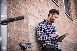 Young man using digital tablet and leaning against brick wall, Munich, Bavaria, Germany