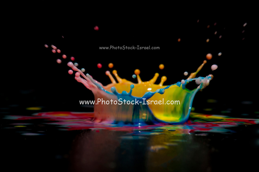 High-speed flash photograph of a colourful liquid droplet. The droplet lands in the liquid and produces a multi colour coronet.