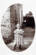 little girl posing at the corner of the house early 1900s France