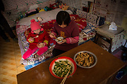 Zhao Jing and her grandmother Li Defang eat lunch while sitting on a bed in their apartment in the Wujianong neighborhood of Hefei, China, on Thursday, Nov. 26, 2015. Cheap housing in the neighbourhood and its closeness to the regional children hospital has made it a popular long term stay option for many families with kids suffering from caner, notably Leukaemia, as Surging health-care costs are turning into one of the biggest threats to the world's second largest economy and its consumers. Surging health-care costs are turning into one of the biggest threats to the world's second largest economy and its consumers.