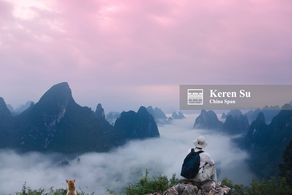 Tourist watching karst hills in morning mist, Li River area, Yangshuo, Guangxi, China