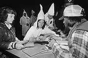 Female Ku Klux Klan members sign a new member to their cause at a rally where Ku Klux Klan members simulated the lynching of an African American with a gorilla masked dummy at a Klan Rally outside Jackson, Georgia. The rally - held in a rural farm field - attracted about 125 people and attempted to both incite violence against blacks and enlarge the local KKK membership.