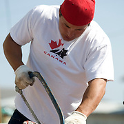Jordin Tootoo grew up in a small village along the Hudson Bay only a hundred miles from the Arctic Circle. The first Inuit to play professionally in the National Hockey League, Tootoo is close to his family and friends to nearly everyone in Rankins Inlet in Northeast Canada. Jordin prepares a frozen fish for the evening meal. <br /> <br /> Image available for licensing and for a personal print. Please Add To Cart and select the size and finish. All prints are delivered directly to you from the printer.