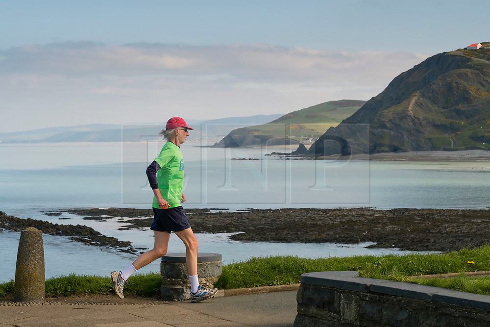 Aberystwyth Wales UK, Friday 07 April 2017<br /> <br /> <br /> UK Weather: Sunny morning in Aberystwyth Wales<br /> <br /> A man jogging on the promenade on a bright sunny spring morning  in Aberystwyth west Wales, . <br /> <br /> High pressure dominates the weather in the UK, promising good weather and temperatures into the low 20ís centigrade over  the coming weekend<br /> <br /> <br /> photo © Keith Morris