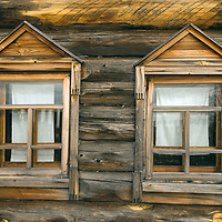 Finely-crafted windows punctuate the log wall of an historic house relocated to the Malye Korely outdoor museum, near the northern port of Arkhangel'sk.