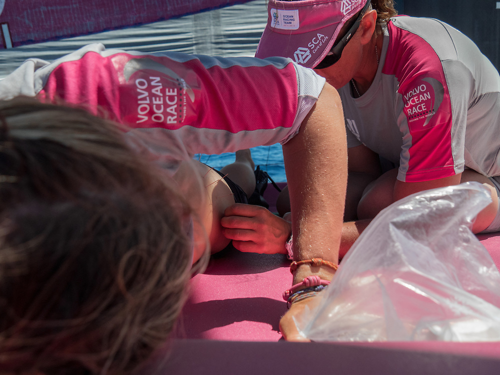 """November, 2014. Leg 2 onboard Team SCA. Dee Caffari """"dry needles"""" Sophie Ciszek to help Sophie's back which has started to cause her some trouble."""