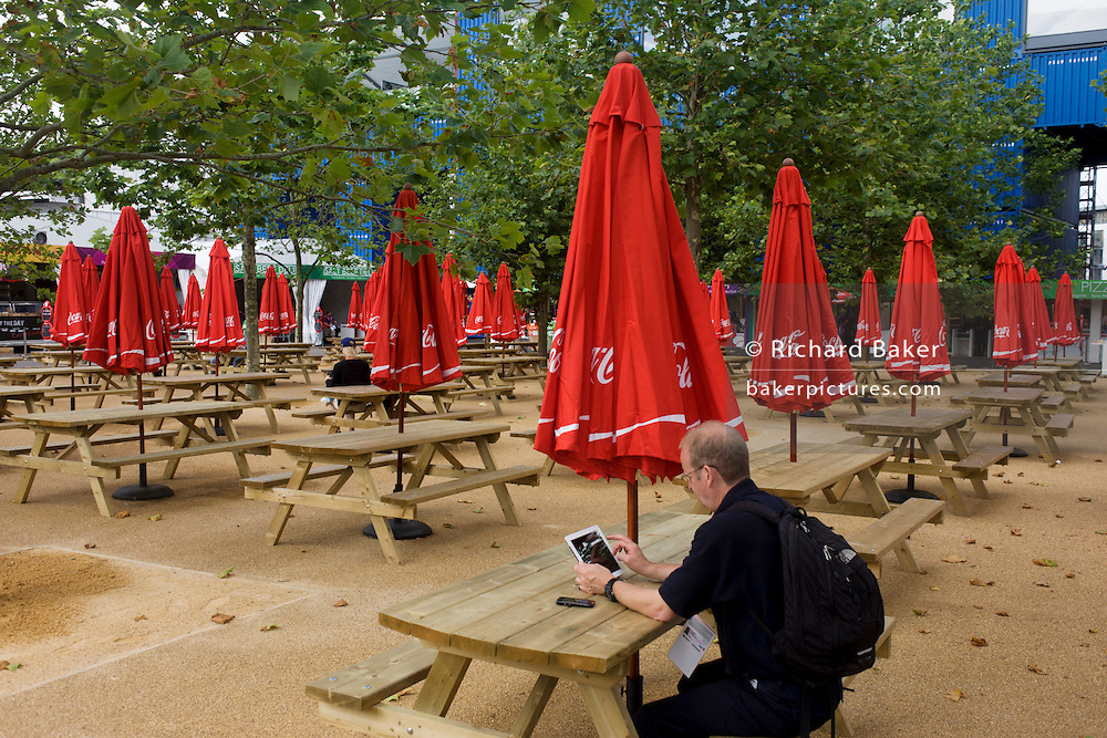 A spectator uses an iPad for results updates under Coca-Cola branded sponsor brolleys in the Olympic Park during the London 2012 Olympics. Coca-Cola Company has supported the Olympic Games began in 1928, now a 92 years association without interruption. This land was transformed to become a 2.5 Sq Km sporting complex, once industrial businesses and now the venue of eight venues including the main arena, Aquatics Centre and Velodrome plus the athletes' Olympic Village. After the Olympics, the park is to be known as Queen Elizabeth Olympic Park.