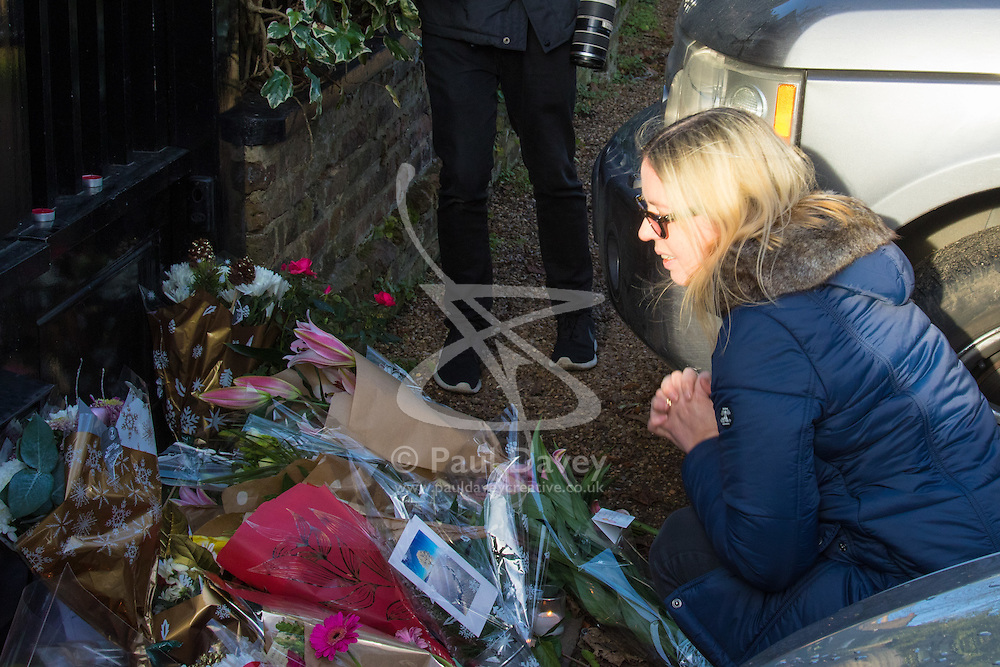 Highgate, London, December 26th 2016. Fans gather outside the London home of pop icon George Michael who died on Christmas day. PICTURED: A woman pauses after laying flowers.