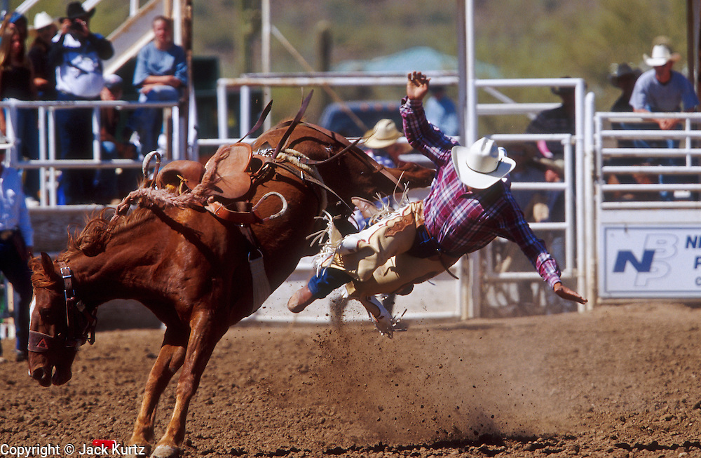 14 APRIL 2002 - CAVE CREEK, ARIZONA, USA: Saddle bronc riding at the Cave Creek Fiesta Days Rodeo in Cave Creek, Arizona, April 14, 2002.  PHOTO BY JACK KURTZ