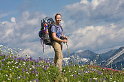 Climber Valerie Wall in a flowering alpine meadow along the Pacific Crest Trail below White Pass, Glacier Peak Wilderness, Washington.