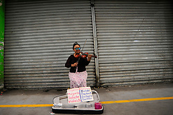 A woman plays a violin at Central de Abasto Market during the daily life amid of Coronavirus outbreak in phase 3. The Central de Abasto is the largest and most important market in Mexico and food provider which has increased its security measures due to recent positive cases among sellers . on April 27, 2020 in Mexico City, Mexico. Photo by Ricardo Castelan Cruz/Eyepix/ABACAPRESS.COM