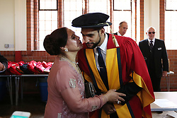 Boxer Amir Khan in his gown receives a kiss from his mother, Zeenat Hussain at Bolton University Victoria Hall before he received an Honorary Degree from Bolton University.