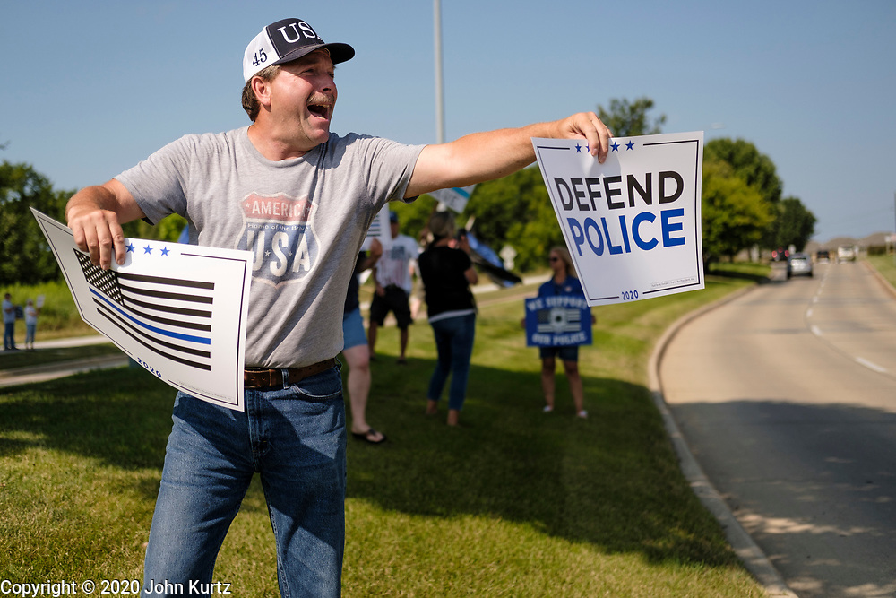 """08 AUGUST 2020 - WEST DES MOINES, IOWA: GARY LEFFLER, from West Des Moines, cheers for law enforcement during a rally to support law enforcement in West Des Moines. About 100 people gathered at the West Des Moines Law Enforcement Center to rally in support of law enforcement. The rally was organized by """"Uplifting Our Police,"""" a local organization that supports law enforcement. They rallied at Des Moines Police headquarters in July. They are planning similar rallies at police stations in the Des Moines metropolitan area.     PHOTO BY JACK KURTZ"""