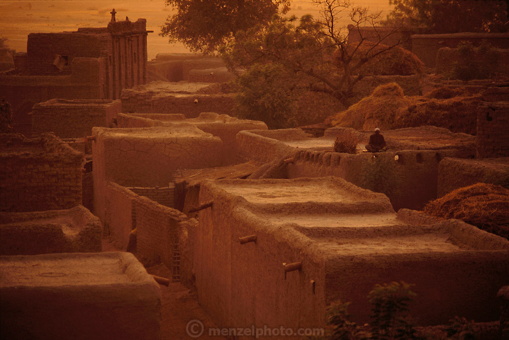 The village of Kouakourou, Mali, at dusk, with a view of its mud brick mosque (Muslim) in the distance. Material World Project.