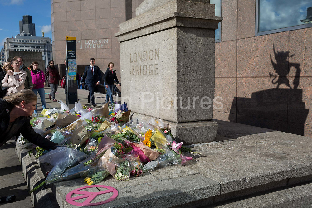 Three days after the terrorist attack in which 7 people died and many others suffered life-changing injuries on London Bridge and Borough Market, shrines of flower tributes grew at various locations around the police crime scene cordan on 6th June 2017, on London Bridge, in the south London borough of Southwark, England. City commuters now back at work walk respectfully and quietly past the floral memorial at the plinth marking the southern boundary of the City of London, the capitals financial district.
