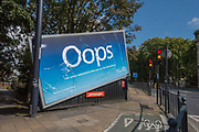 O2 launches multimillion-pound 'Oops' campaign promoting screen replacement service with a half fallen  billboard and fake cracked screen captured on 11th September 2017 in London, United Kingdom. Advert featured on the corner of Commercial Road and Salmon Lane along the A13.