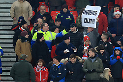 A steward makes a fan take down his sign in the stands during the Premier League match at the bet365 Stadium, Stoke.