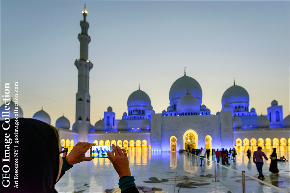 A visitor photographs the Sheikh Zayed Grand Mosque in Abu Dhabi—one of the largest mosques in the world.  Reflecting the architectural styles of various Muslim civilizations, the mosque borrows from the traditions of Turkey, Morocco, Pakistan, and Egypt, among other Islamic countries.