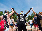 06 JUNE 2020 - DES MOINES, IOWA: A member of Black Lives Matter fist bumps people arriving at the Iowa State Capitol for a Black Lives Matter rally after a march through downtown. More than 1,000 protesters marched through downtown Des Moines to the state capitol to demand an end to police violence against Black people. The march was organized by Black Lives Matter and honored George Floyd, the unarmed Black man killed by Minneapolis police on 25 May 2020.        PHOTO BY JACK KURTZ