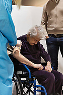 First day of vaccination for the over-80s in Auditorum Park of Musica in Roma on 15th of February, Italy. A healt worker administers a Moderna vaccine dose to an old woman.